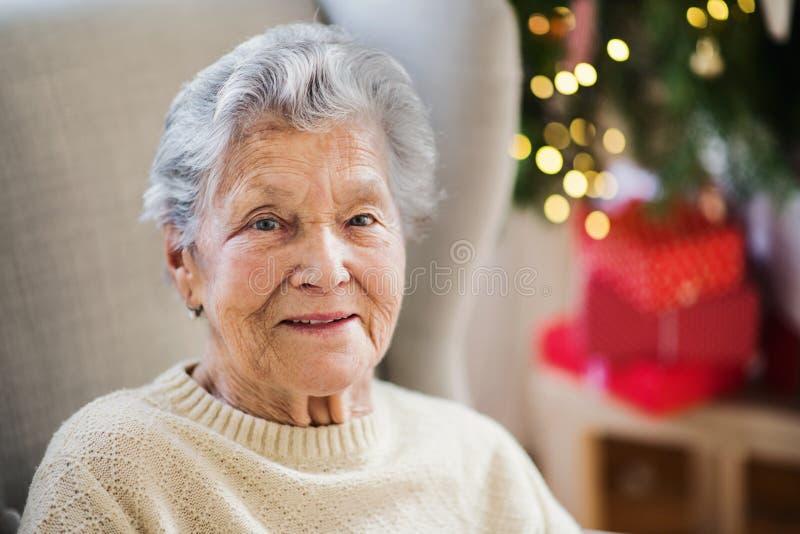 Un retrato de una mujer mayor en silla de ruedas en casa en el tiempo de la Navidad fotografía de archivo