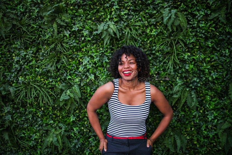 Un retrato de una mujer negra que se opone al fondo verde del arbusto se va fotografía de archivo libre de regalías