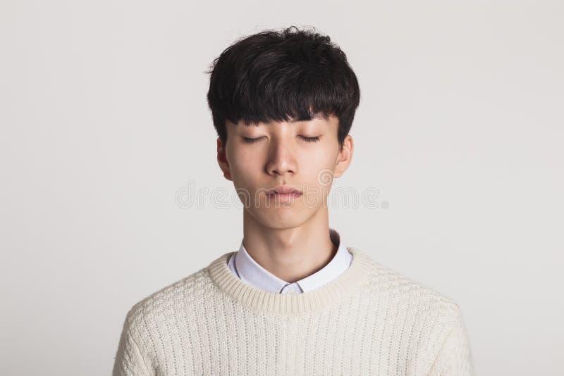 Un retrato del estudio de un hombre joven asiático que agarra sus ojos y pensamiento foto de archivo