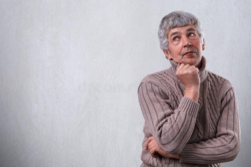 Un retrato del hombre mayor soñador pensativo que se coloca sobre el fondo blanco con el espacio de la copia para su anuncio Homb fotos de archivo libres de regalías