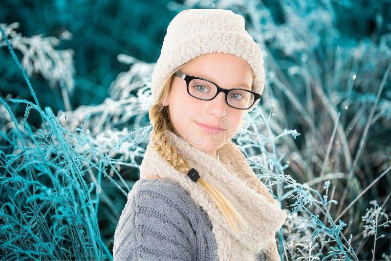 Un retrato del invierno de la muchacha hermosa joven con el suéter y los vidrios de lana de la bufanda foto de archivo libre de regalías