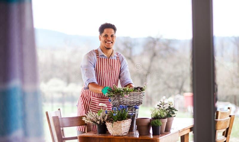 Un retrato del jardinero del hombre joven al aire libre en casa, plantando las flores fotografía de archivo