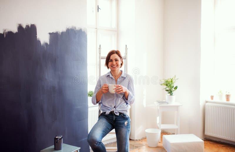 Un retrato del negro de la pared de la pintura de la mujer joven Un inicio de la peque?a empresa imagen de archivo