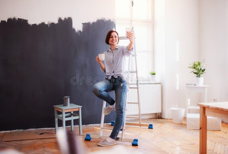 Un retrato del negro de la pared de la pintura de la mujer joven Un inicio de la peque?a empresa foto de archivo