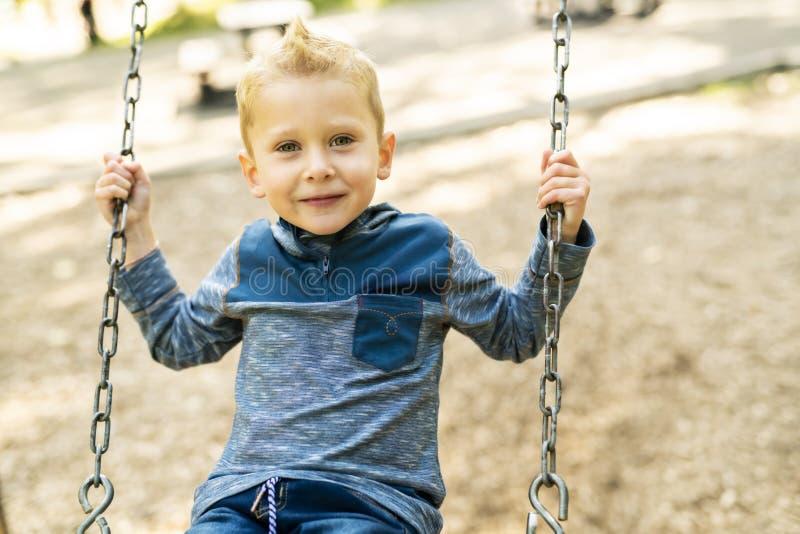 Un retrato del niño pequeño sonriente feliz en el oscilación imagenes de archivo