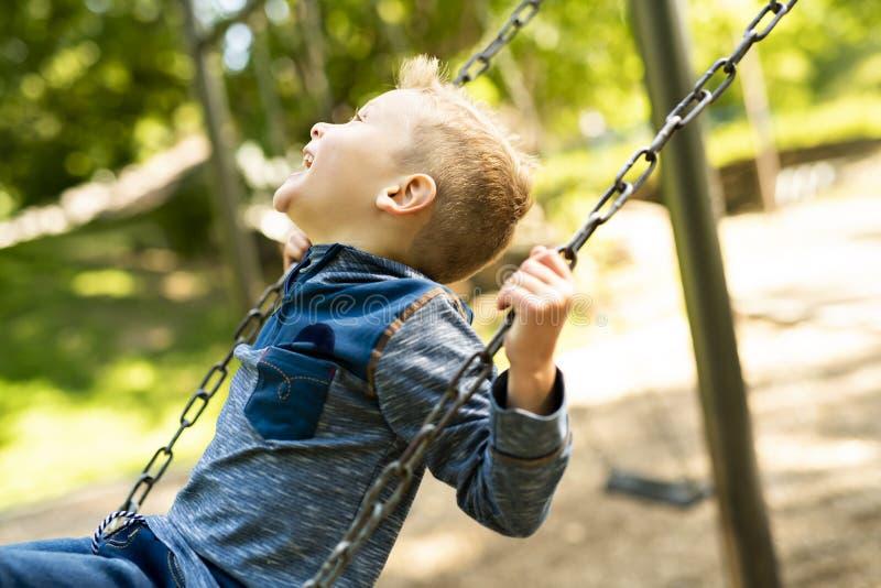 Un retrato del niño pequeño sonriente feliz en el oscilación fotografía de archivo