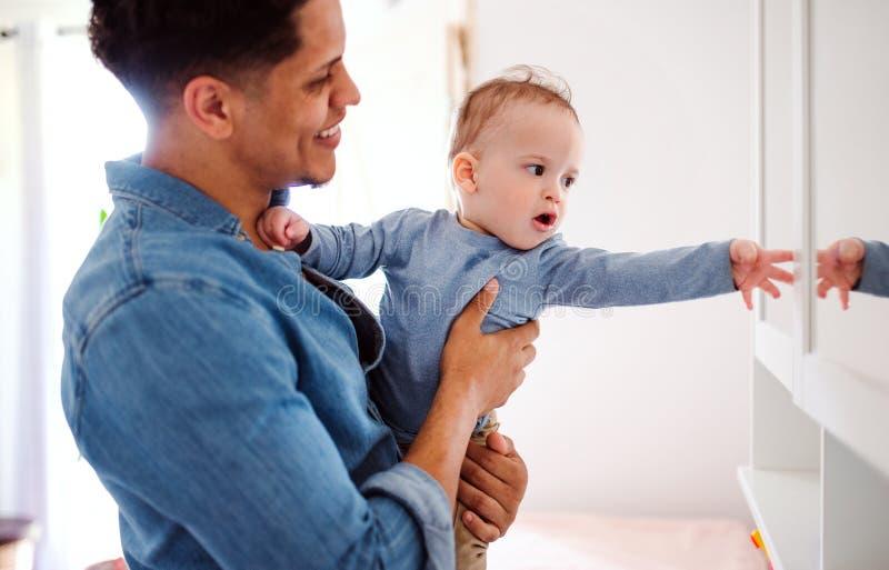 Un retrato del padre y del peque?o hijo del ni?o dentro en casa, jugando fotografía de archivo