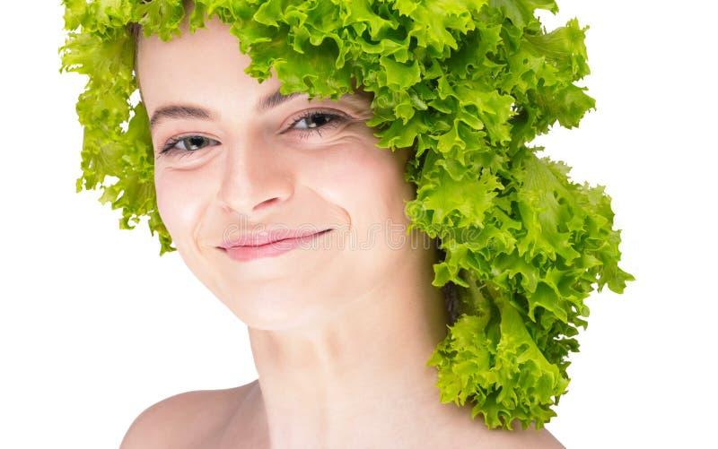 Un retrato grande de una muchacha con una ensalada en su cabeza en el aislamiento vegetariano Consumición sana Dieta para el vera imagenes de archivo