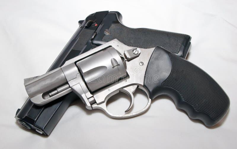 Un revólver inoxidable de 357 botellas dobles encima de una pistola semiautomática negra de 40 calibres fotos de archivo libres de regalías
