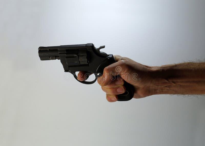 Un revólver listo para encender en una mano del ` s del hombre imagen de archivo