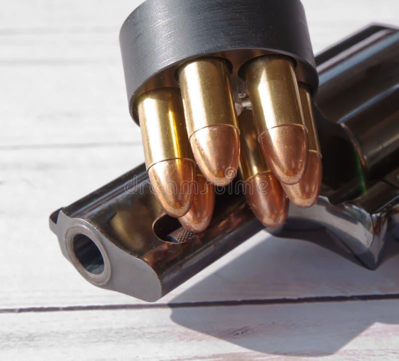 Un revolver noir partiel montré sur un fond en bois avec un chargeur de vitesse sur le dessus s'il photo stock