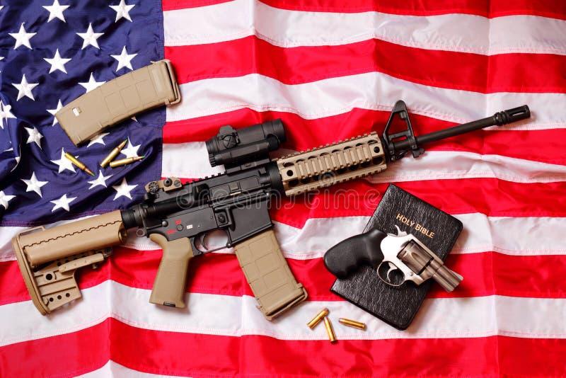 Rifle de AR, una biblia y una pistola en bandera americana imágenes de archivo libres de regalías
