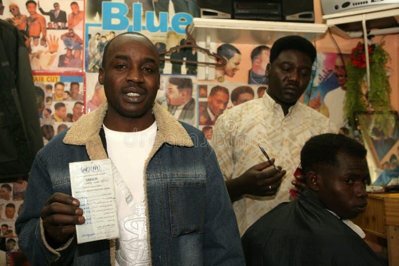 Un rifugiato sudanese che lavora in un negozio di barbiere fotografia stock