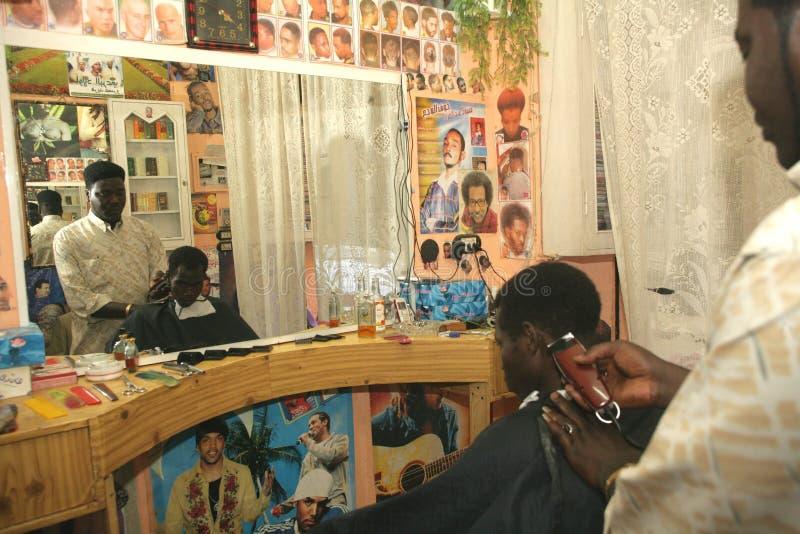Un rifugiato sudanese che lavora in un negozio di barbiere immagine stock libera da diritti