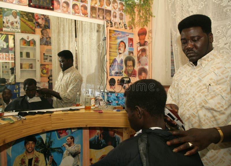 Un rifugiato sudanese che lavora in un negozio di barbiere fotografie stock libere da diritti