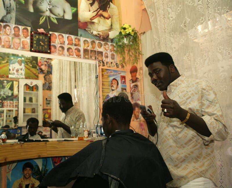 Un rifugiato sudanese che lavora in un negozio di barbiere immagini stock libere da diritti