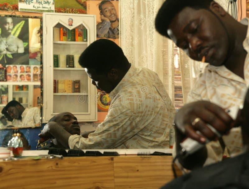 Un rifugiato sudanese che lavora in un negozio di barbiere fotografie stock