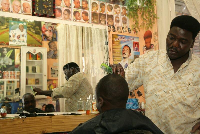 Un rifugiato sudanese che lavora in un negozio di barbiere immagini stock