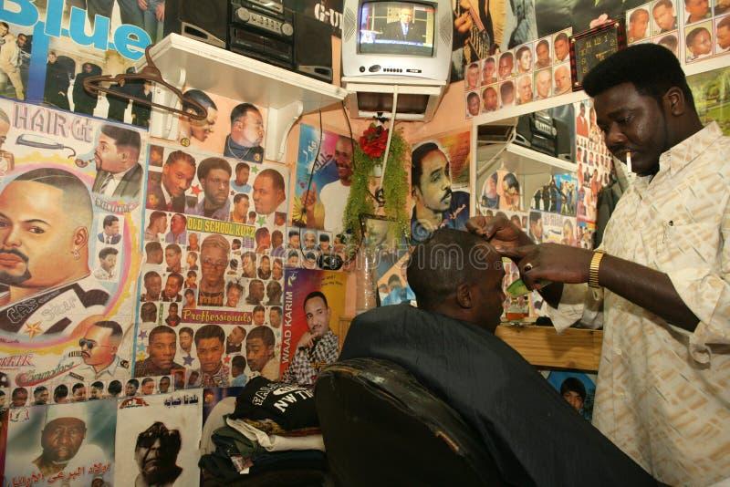 Un rifugiato sudanese che lavora in un negozio di barbiere immagine stock