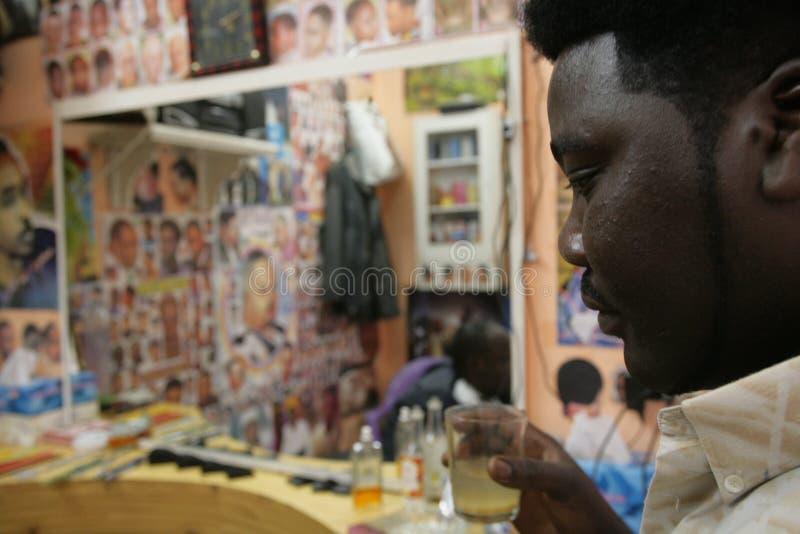 Un rifugiato sudanese che lavora in un negozio di barbiere fotografia stock libera da diritti