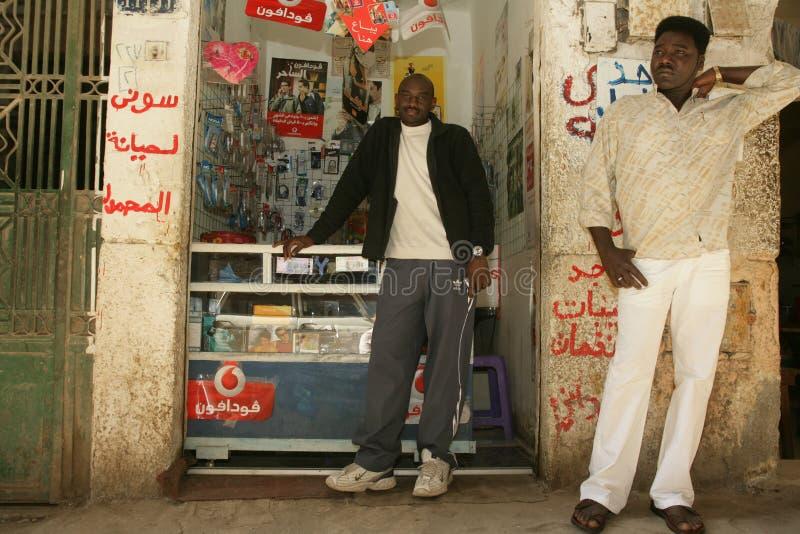 Un rifugiato sudanese ed il suo amico davanti al suo telefono cellulare comperano immagine stock libera da diritti