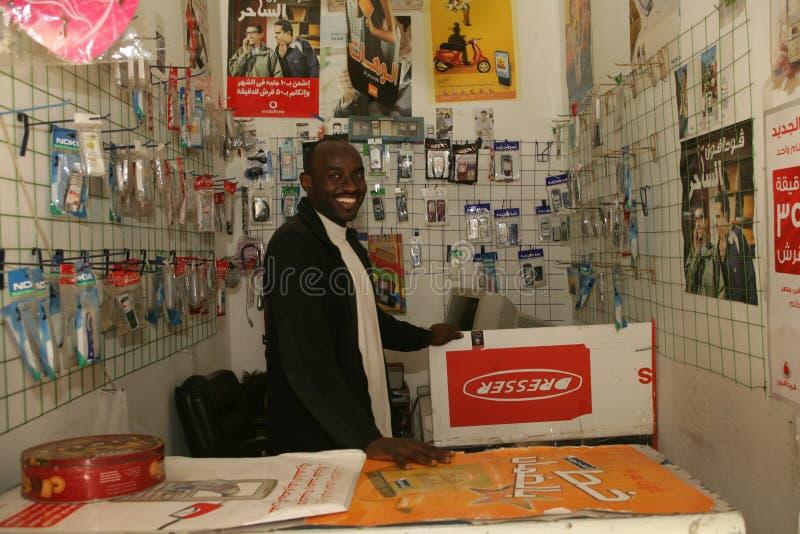 Un rifugiato sudanese nel suo negozio del telefono cellulare immagine stock