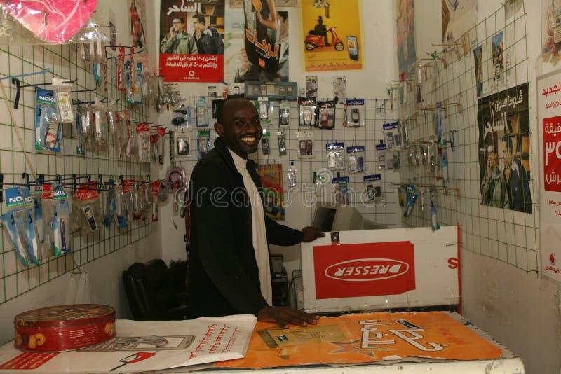 Un rifugiato sudanese nel suo negozio del telefono cellulare fotografie stock