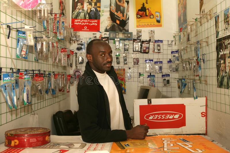 Un rifugiato sudanese nel suo negozio del telefono cellulare immagini stock