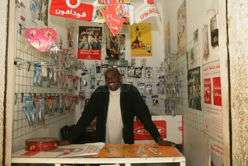 Un rifugiato sudanese nel suo negozio del telefono cellulare fotografia stock