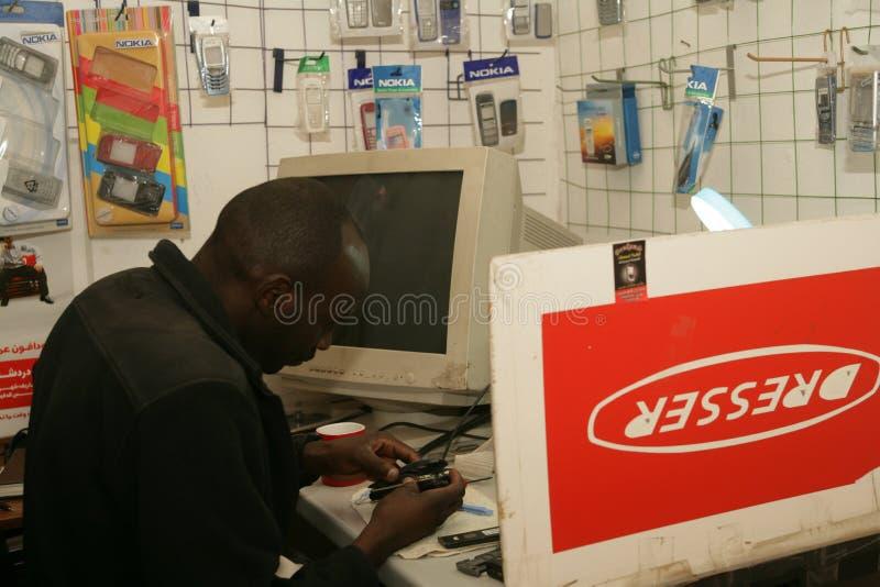 Un rifugiato sudanese nel suo negozio del telefono cellulare immagini stock libere da diritti