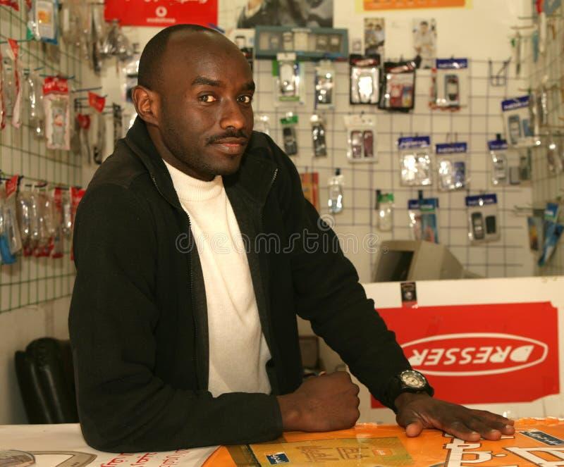 Un rifugiato sudanese nel suo negozio del telefono cellulare fotografia stock libera da diritti