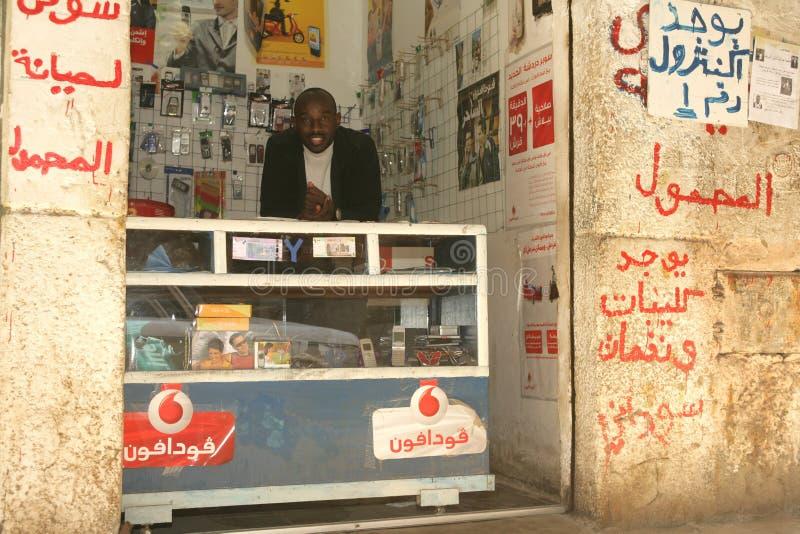 Un rifugiato sudanese in suoi accessori del telefono cellulare compera immagini stock libere da diritti