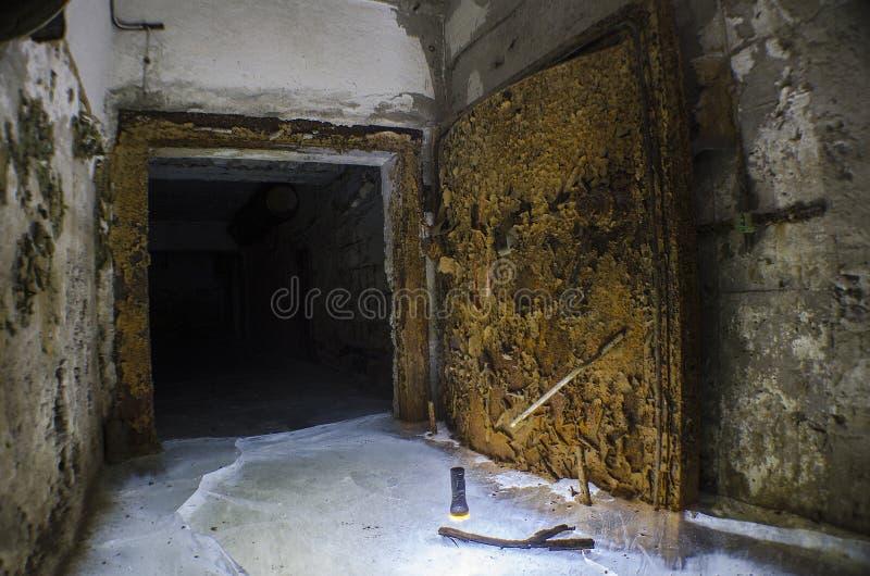Un rifugio antiaereo sommerso abbandonato nel seminterrato, con una porta ermetica arrugginita immagine stock libera da diritti