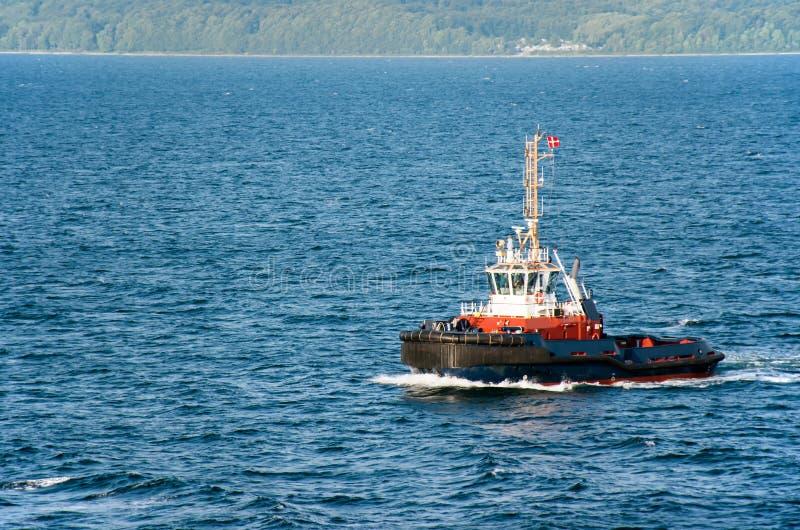 Un rimorchiatore con una bandiera danese traversa sul mare, nei precedenti che la costa boscosa può essere veduta fotografie stock libere da diritti