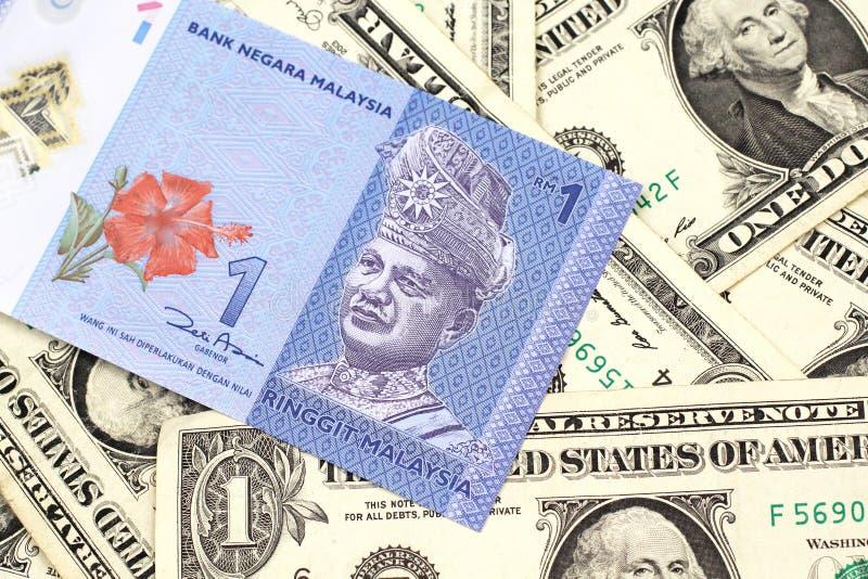 Un ringgit malese su un fondo delle banconote in dollari una fotografia stock