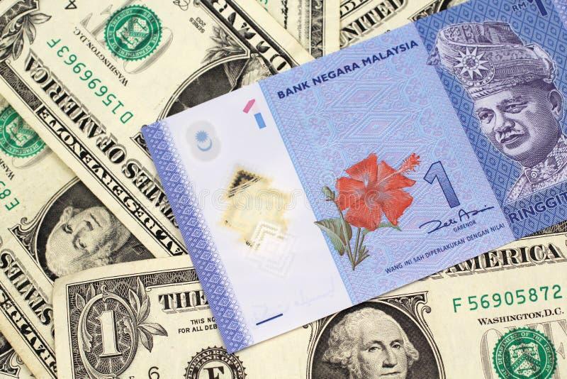 Un ringgit malese su un fondo delle banconote in dollari una fotografie stock libere da diritti