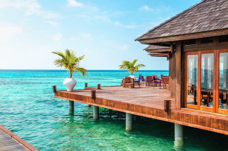 Un ristorante di legno sull'acqua contro il contesto delle acque azzurrate dell'Oceano Indiano, Maldive fotografie stock libere da diritti