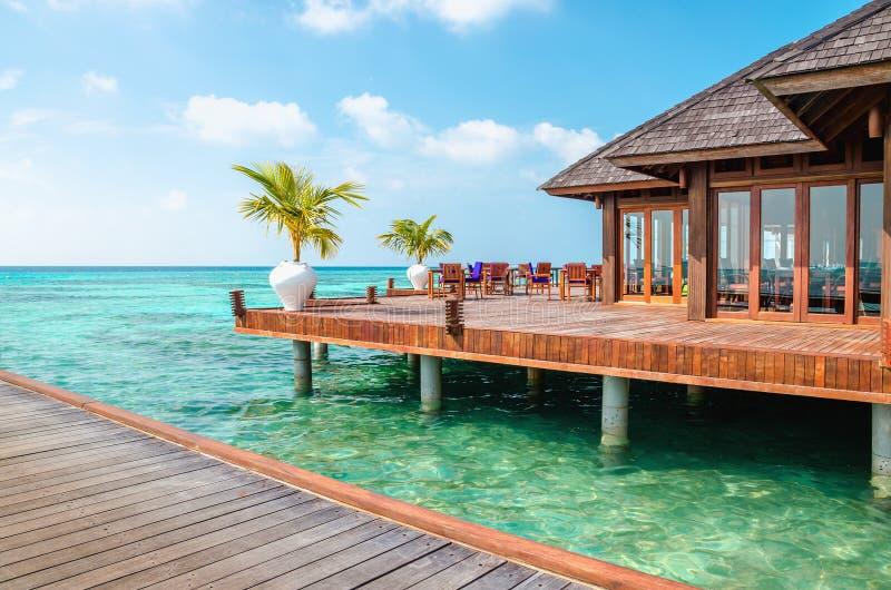 Un ristorante di legno sull'acqua contro il contesto delle acque azzurrate dell'Oceano Indiano, Maldive fotografie stock