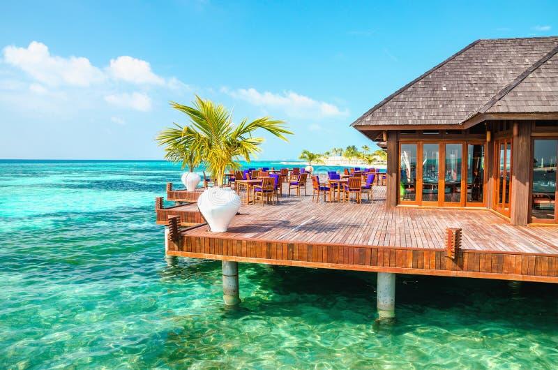 Un ristorante di legno sull'acqua contro il contesto delle acque azzurrate dell'Oceano Indiano, Maldive fotografia stock libera da diritti