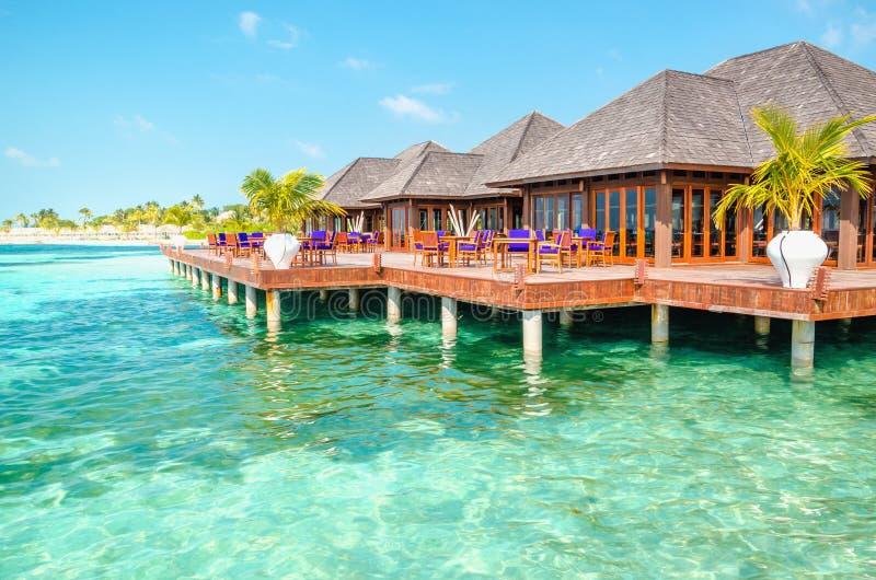 Un ristorante di legno sull'acqua contro il contesto delle acque azzurrate dell'Oceano Indiano, Maldive immagini stock