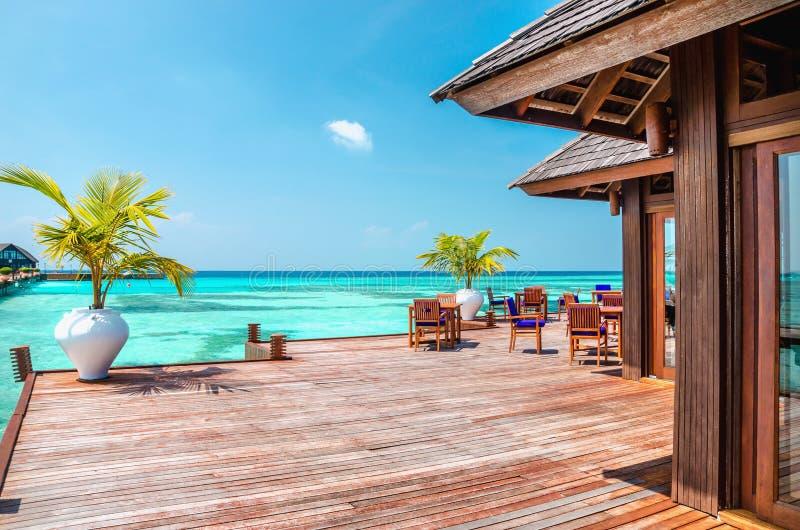 Un ristorante di legno sull'acqua contro il contesto delle acque azzurrate, Oceano Indiano, Maldive fotografie stock