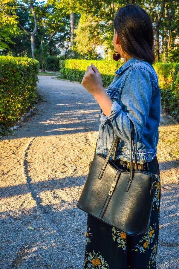 Un ritratto all'aperto di una giovane donna, portando un vestito floreale e un rivestimento del denim, tenenti una borsa immagini stock