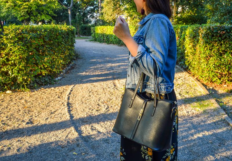 Un ritratto all'aperto di una giovane donna, portando un vestito floreale e un rivestimento del denim, tenenti una borsa fotografia stock