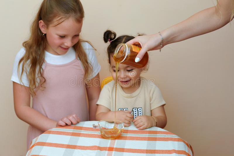 Un ritratto alto vicino della bambina sveglia divertente due che considera la mano della donna che versa miele fresco dal baratto immagini stock