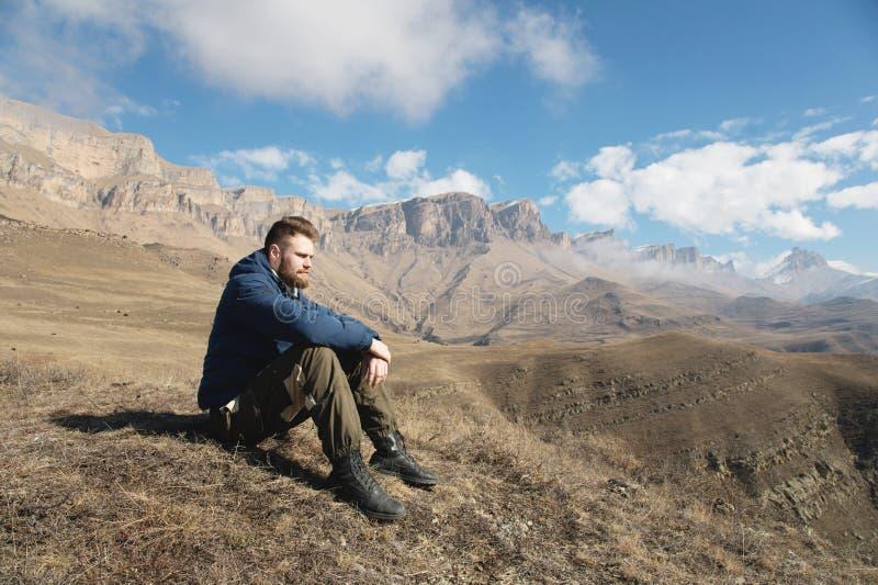 Un ritratto dei pantaloni a vita bassa barbuti alla moda che si siedono su una roccia contro il contesto delle rocce epiche e che fotografie stock libere da diritti