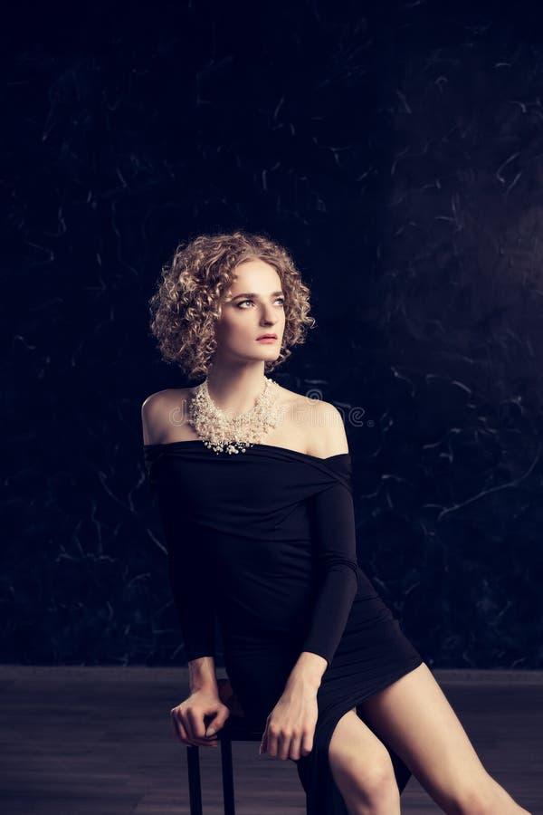 Un ritratto del modello del tipo del transessuale con capelli biondi che posano seduta in un vestito nero su un fondo scuro fotografia stock libera da diritti