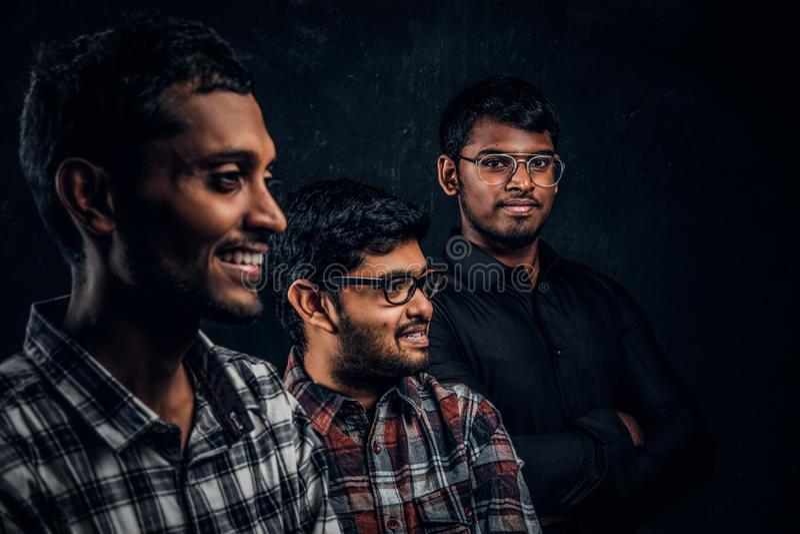 Un ritratto del primo piano di tre studenti indiani felici che indossano l'abbigliamento casual contro una parete scura fotografia stock libera da diritti
