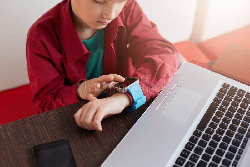 Un ritratto del ragazzino in camicia rossa che si siede alla tavola di legno che indossa orologio elettronico che guarda allora m fotografie stock