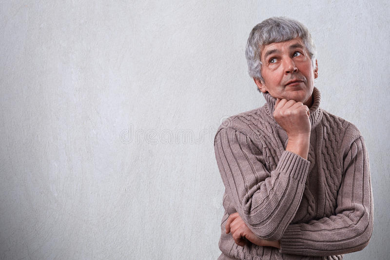 Un ritratto dell'uomo senior vago premuroso che controlla fondo bianco con lo spazio della copia per la vostra pubblicità Uomo ma fotografie stock libere da diritti