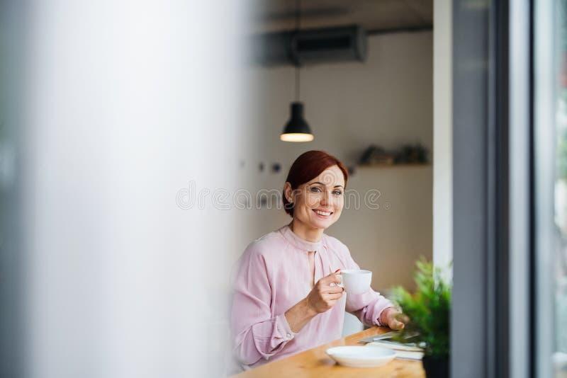 Un ritratto della donna con caffè che si siede alla tavola in un caffè, facendo uso del computer portatile fotografie stock libere da diritti